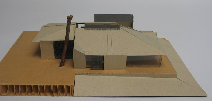 Working model for house with big roof and sliding screens for glass protection.  The large tree is existing, still.  Low view to water.