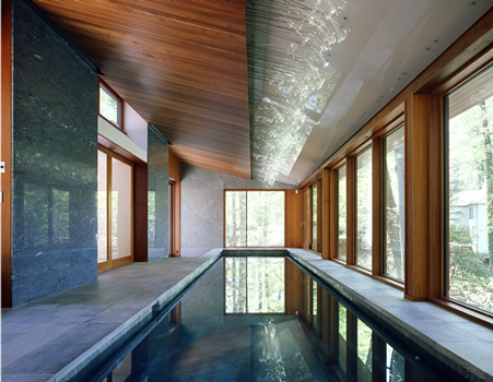 Photo: Catherine Tighe.  Due to the slope of the site, the swimmer is 12' above grade at the deep end of the pool near the window.  The pool finish, applied by hand, is a tinted plaster in a bluish-grey color achieved by mixing several standard dry pigments.  The room is heated by the pool water and the radiant heat in the concrete floor slab.  The floor and pool coping is green quartzite tile; the walls are a combination of the Brazilian Azul du Mar marble and the green Costa Esmerelda granite.  The wood frame of the Duratherm sliding and fixed doors and windows is in a clear finish mahogany; the tongue-and-groove ceiling is made from sapelle, as are the wood panels above the east-facing openings.  The glass ceiling panels are laminated with a translucent inner layer, minimally gapped for air flow, and held in place to a Uni-Strut steel system above with stainless steel Tri-Pyramid standoffs.  Leveling of the glass panels was challenging and was made possible by the adjustable anchors.  At the ceiling plane change, 520 stainless steel rods threaded with fiber-optic strands light the space.  The dots of light reflect off the ceiling glass, the wall glazing and the water, particularly as the outside light level dims.