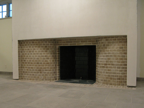 Incomplete basement fireplace with curved limestone side walls