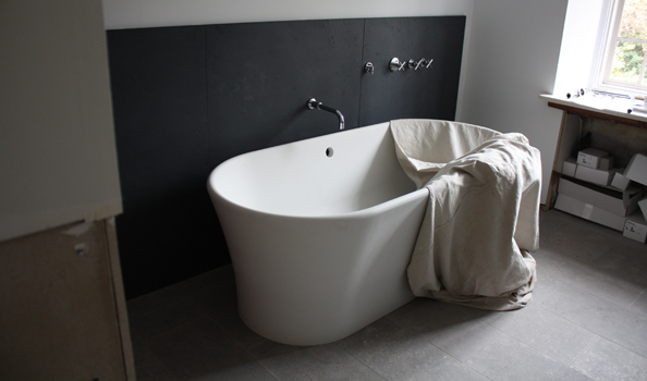 White resin tub with plaster-like finish against black Pennsylvania slate wainscot